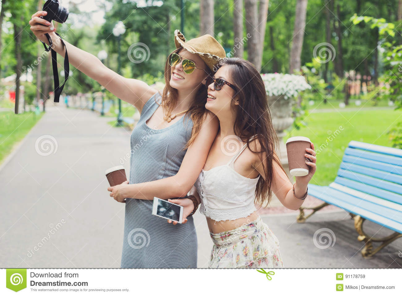 2689df2248 Two girls friends outdoors take selfie with smartphone. Young female  tourists in boho chic fashion clothes