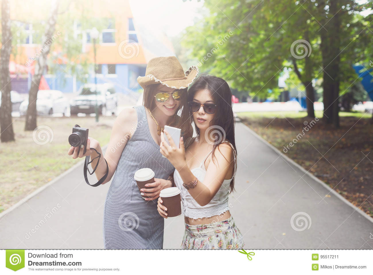 0861327e47 Two girls friends take selfie with smartphone. Young female tourists in  boho chic fashion clothes