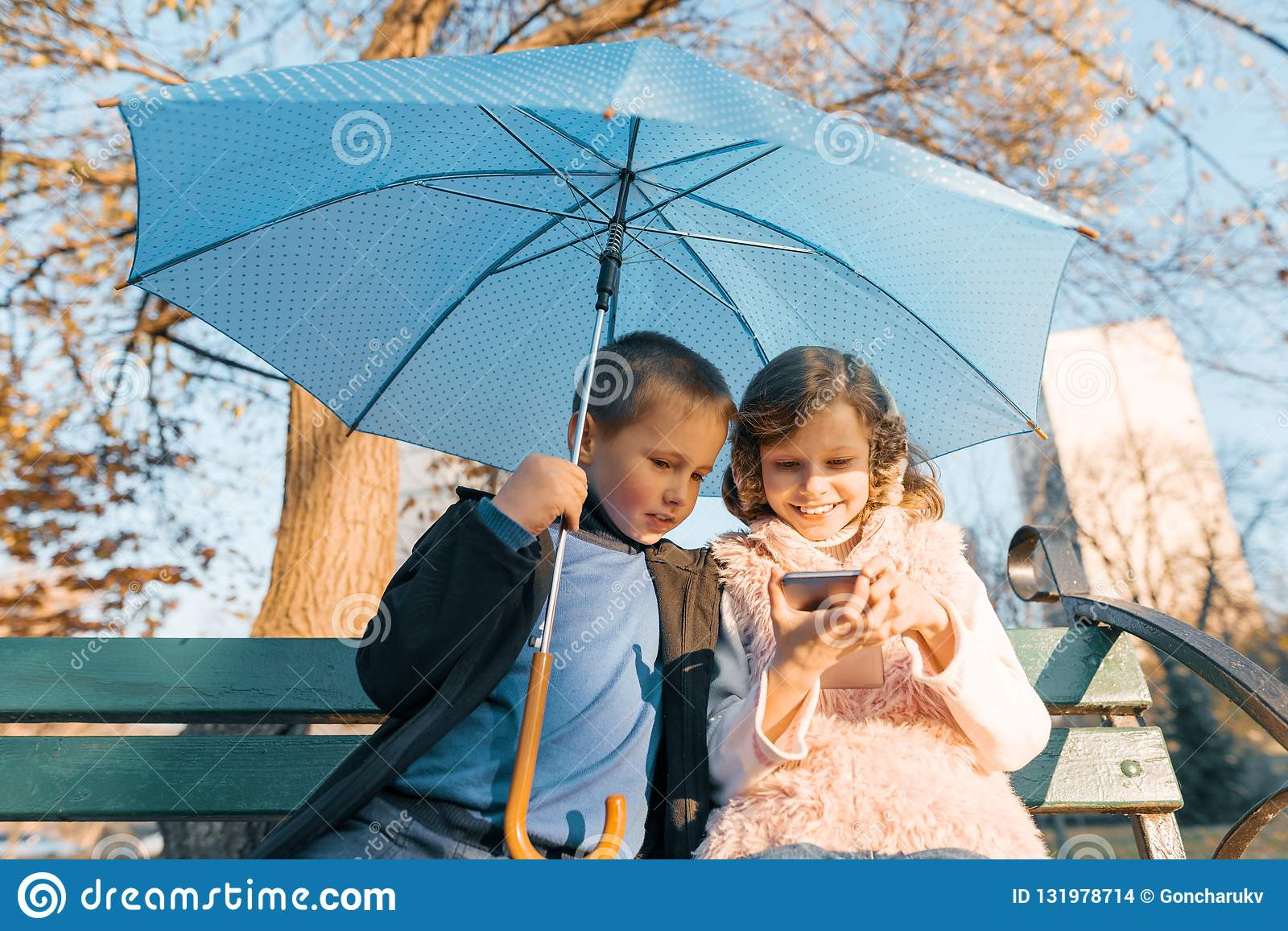 Outdoor portrait of two smiling children of boy and girl, sitting under an umbrella on bench in the park, looking at smartphone,