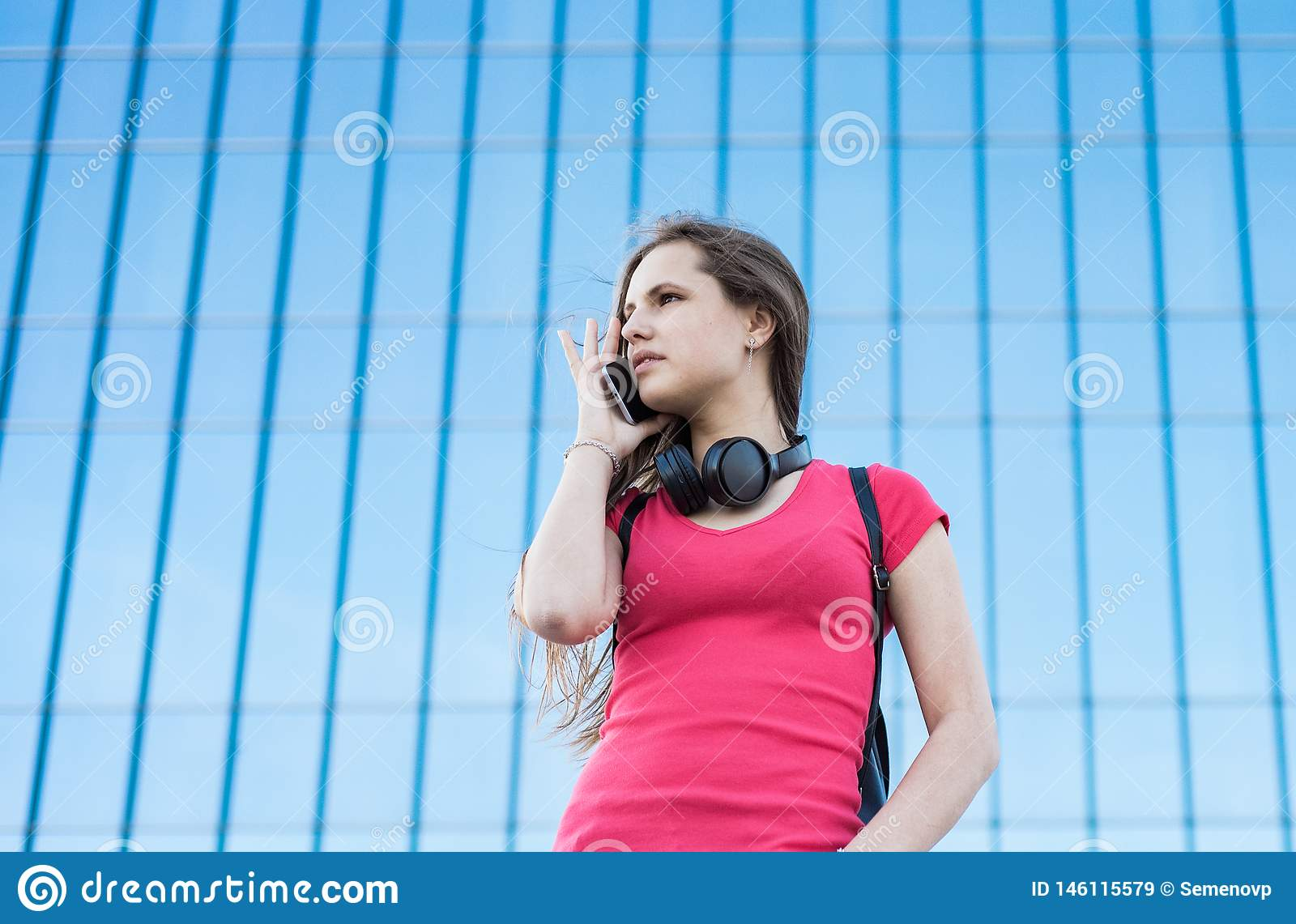 Portrait of young teenager brunette girl in coral t-shirt with long hair. girl on city talking on the smart phone. Glass building