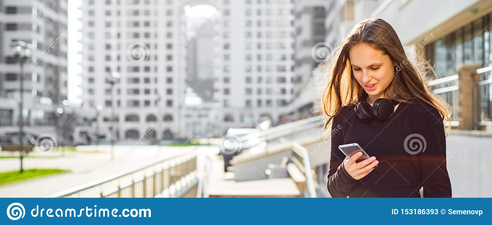 Outdoor portrait of young teenager brunette girl with long hair. girl on city in black dress looking on the smartphone in the stre