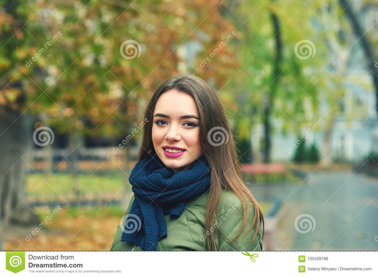 Outdoor portrait of young woman in autumnal city