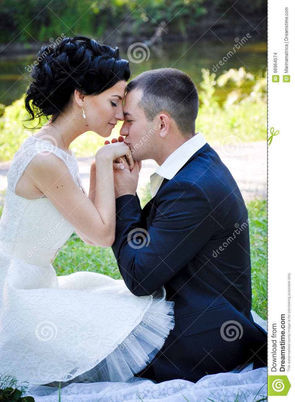 Outdoor sensual portrait of young beautiful couple in love posing in summer park boyfriend kissing his girlfriend