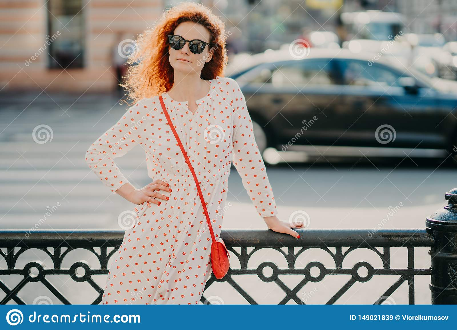 Outdoor shot of satisfied redhead woman keeps one hand on waist, other on street hence, poses over blurred urban setting, wears