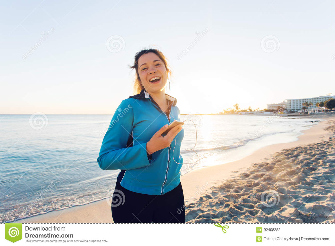 Outdoor sport, fitness gadget and people concept - Smiling female fitness holding smartphone with earphones.
