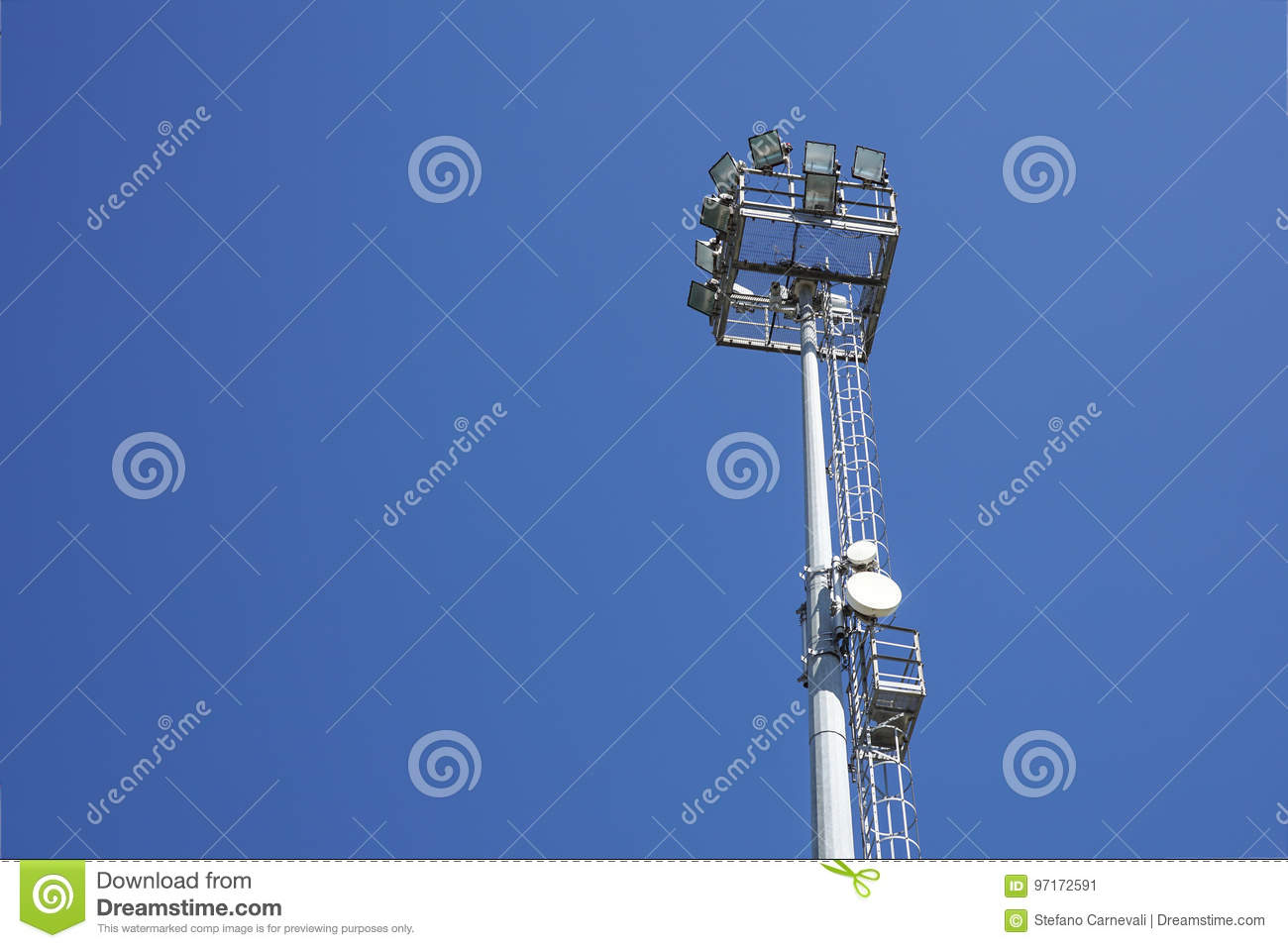 Outdoor stadium lights and telecommunication tower against daytime blue sky. 58ba597b51ef7