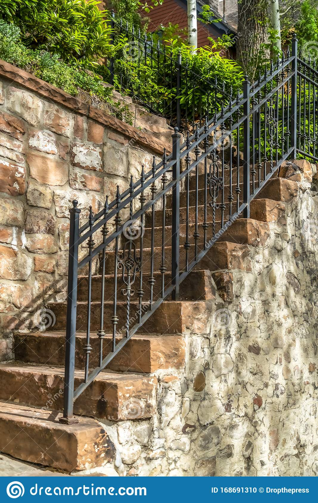 Outdoor Staircase With Stone Steps And Black Metal Railing Against A Fence Stock Photo Image Of Sunlight Green 168691310