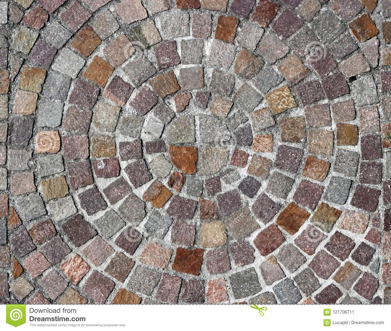 Outdoor stone flooring of porphyry cubes made with a round design, with circles that becomes larger starting from the center