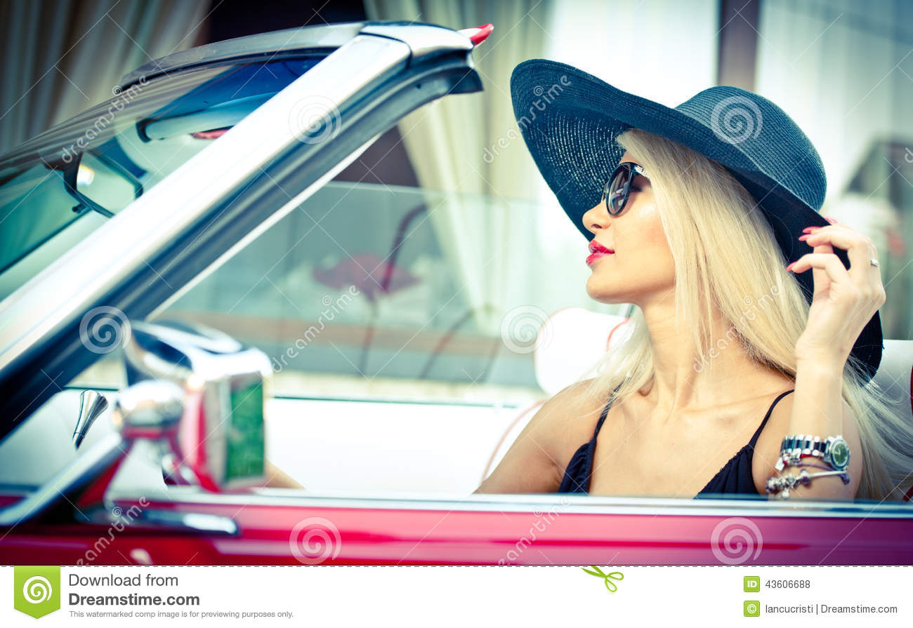 Outdoor summer portrait of stylish blonde vintage woman driving a convertible red retro car. Fashionable attractive fair hair girl