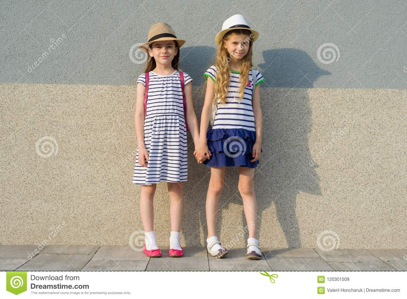 Outdoor summer portrait of two happy girl friends 7, 8 years holding hands. Girls in striped dresses, hats with backpack,