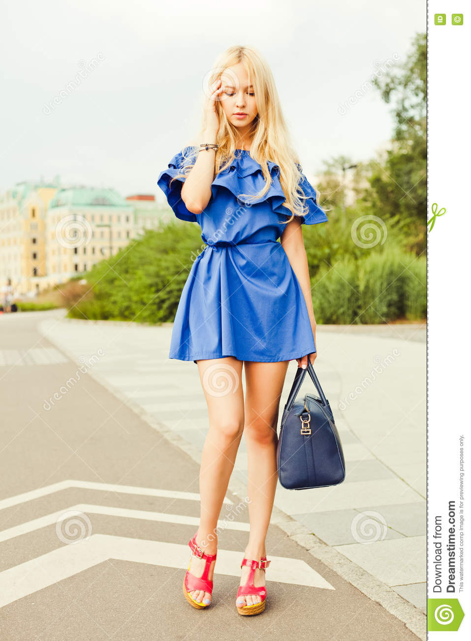 Outdoor summer smiling lifestyle portrait of pretty young woman with big blue handbag. Long blond hairs, blue outfit in