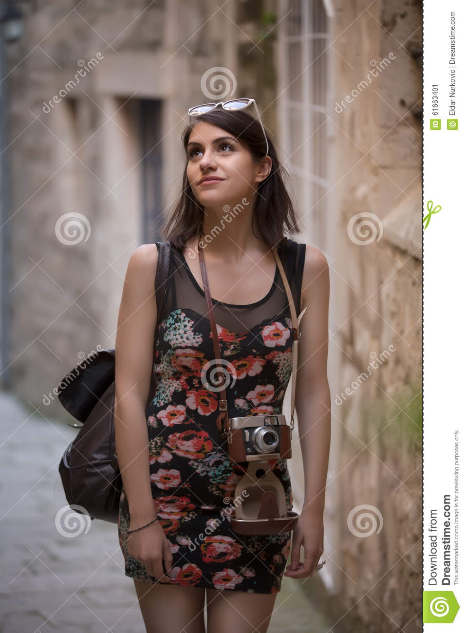 Outdoor summer smiling lifestyle portrait of pretty young woman having fun in the city in Europe with vintage analog camera. Woman