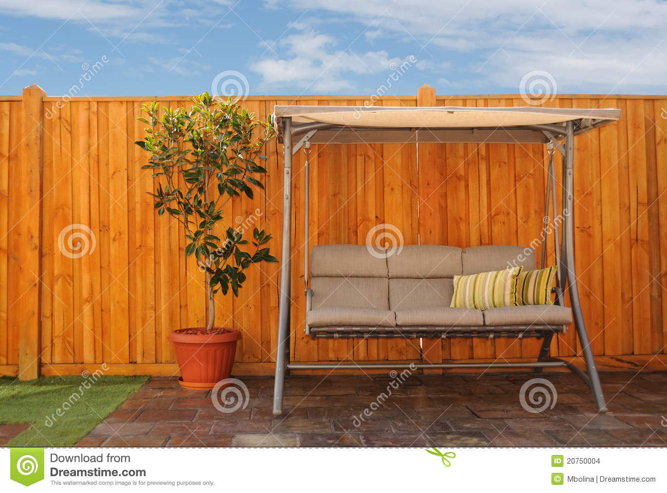 outdoor swing chair in front of wooden cedar fence stock images