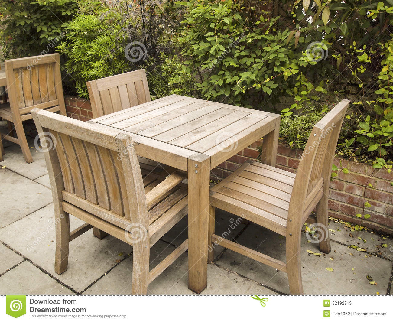 Photo of old wooden table and chairs outdoors with brick barrier and ...