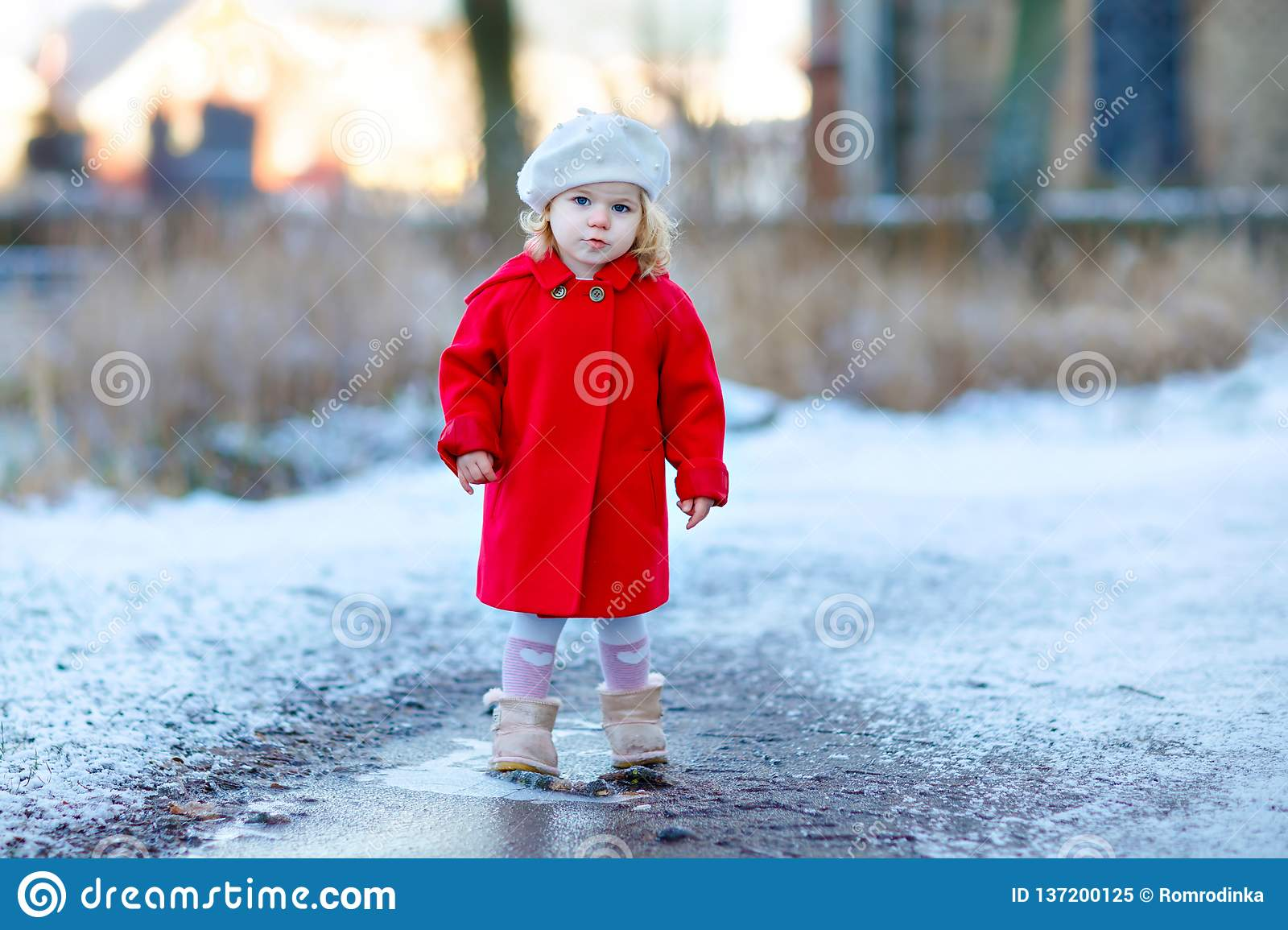 317c3186a9a Outdoor winter portrait of little cute toddler girl in red coat and white  fashion hat barret