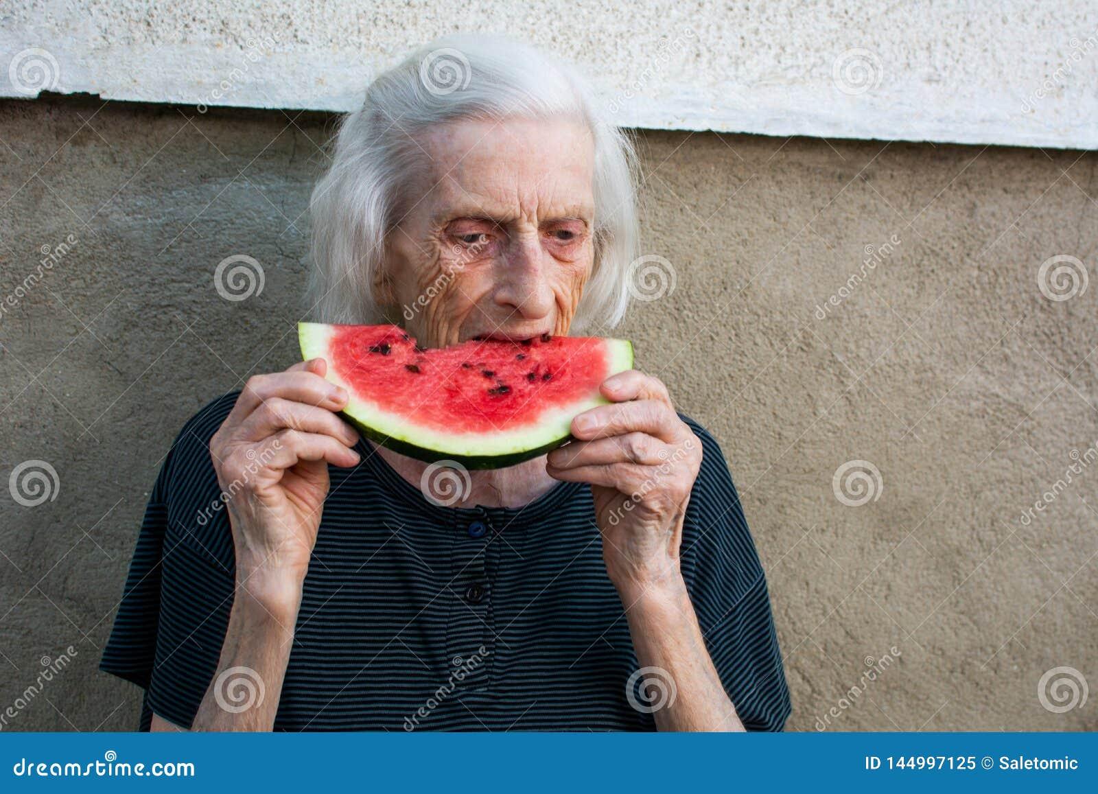 Старшая женщина есть арбуз outdoors