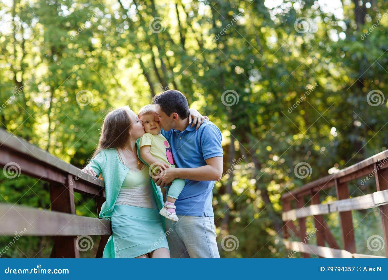 Outdoors портрета семьи мамы и папы целуя их дочь