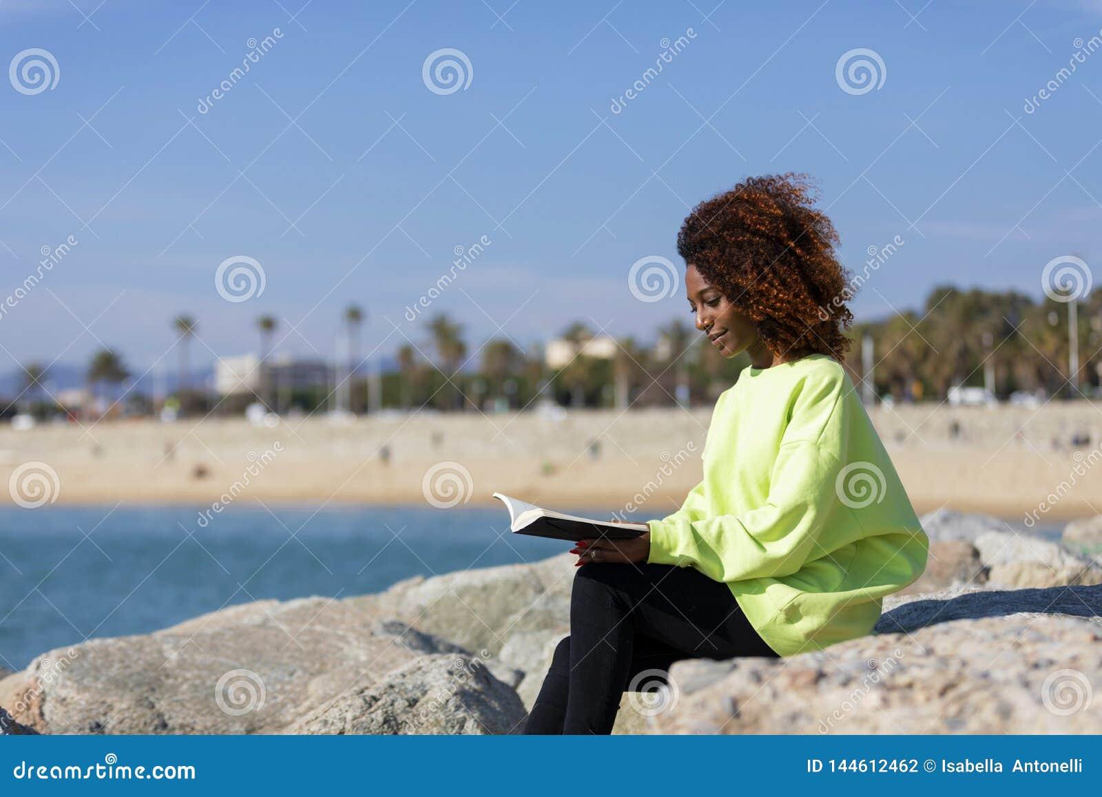 Взгляд со стороны молодой курчавой афро женщины сидя на волнорезе держа книгу пока усмехающся и смотрящ прочь outdoors
