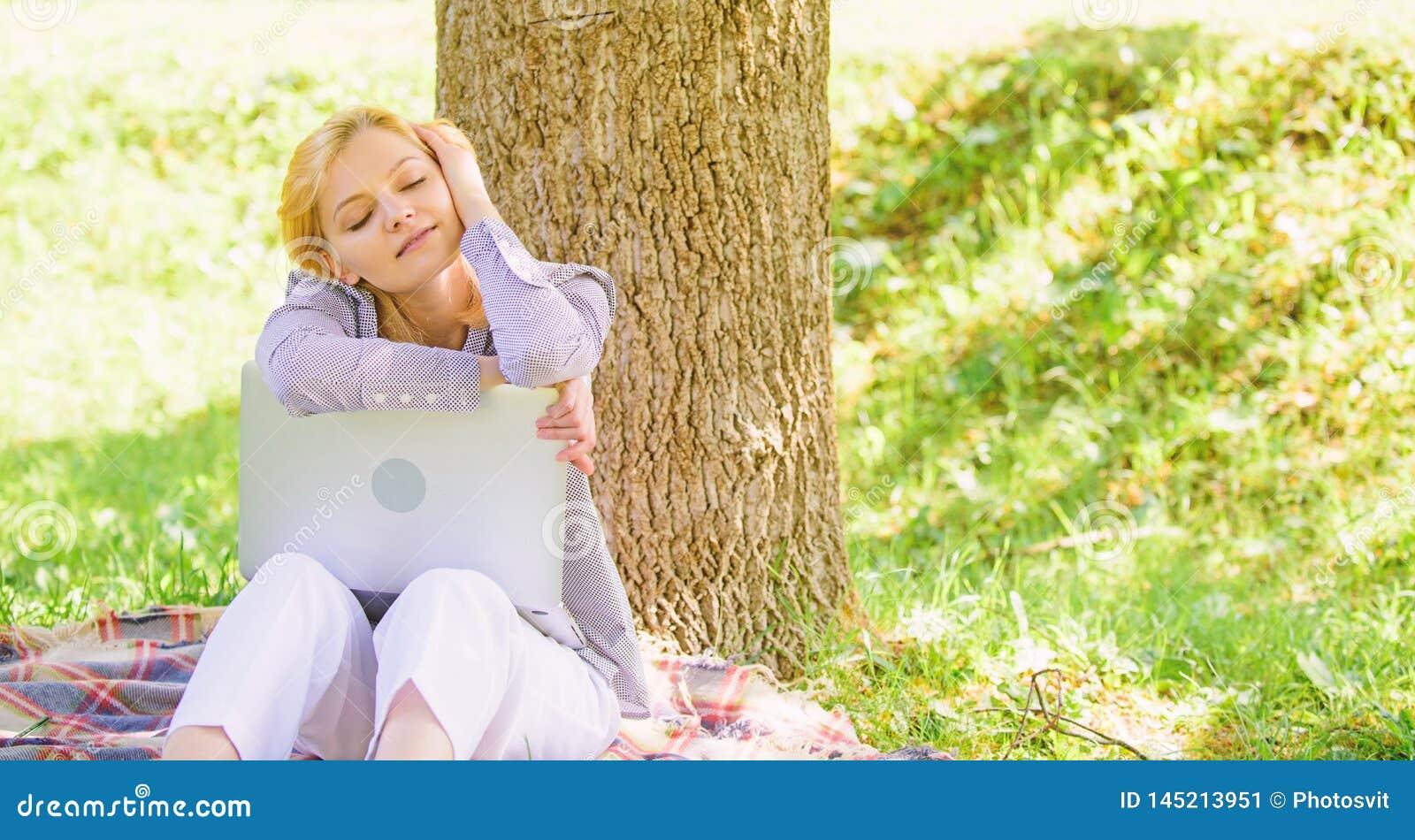 Ноутбук девушки мечтая в парке сидит на траве Мечта об успешном проекте Женщина мечтательная с работой ноутбука outdoors