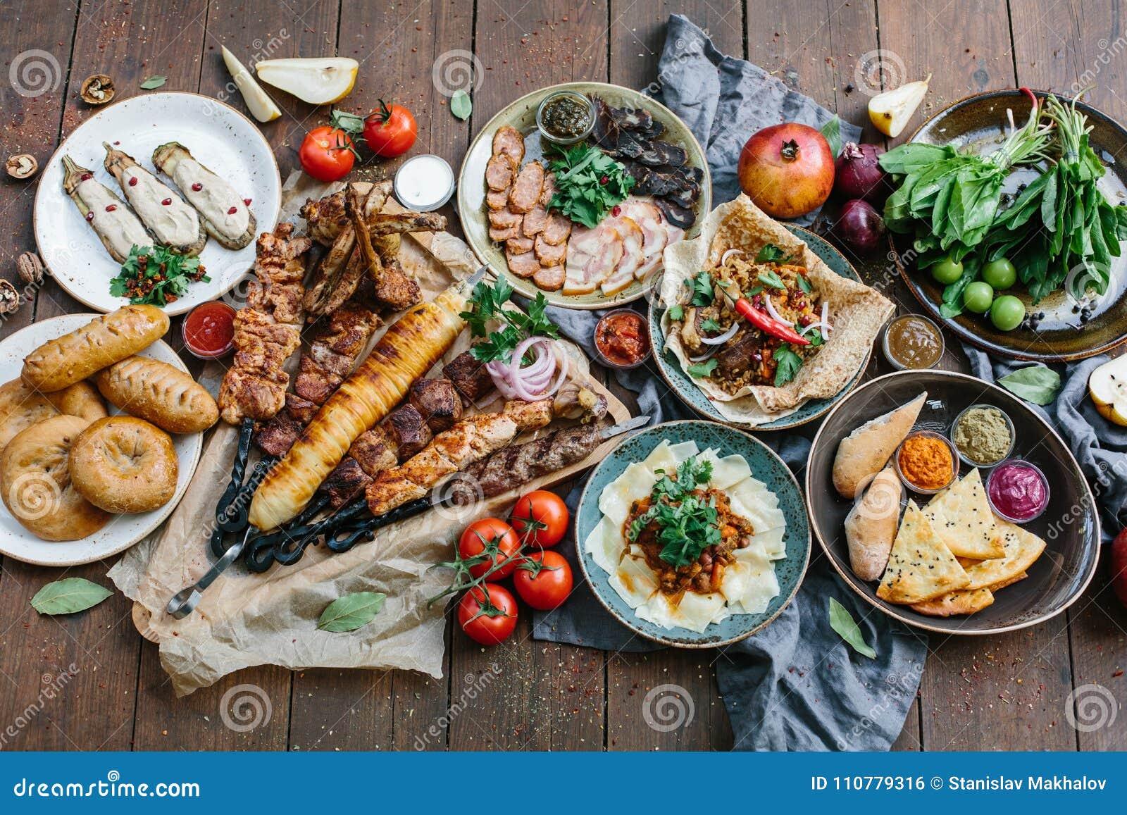 Outdoors karmowy pojęcie Apetyczny barbecued stek, kiełbasy i piec na grillu warzywa na drewnianym pyknicznym stole,