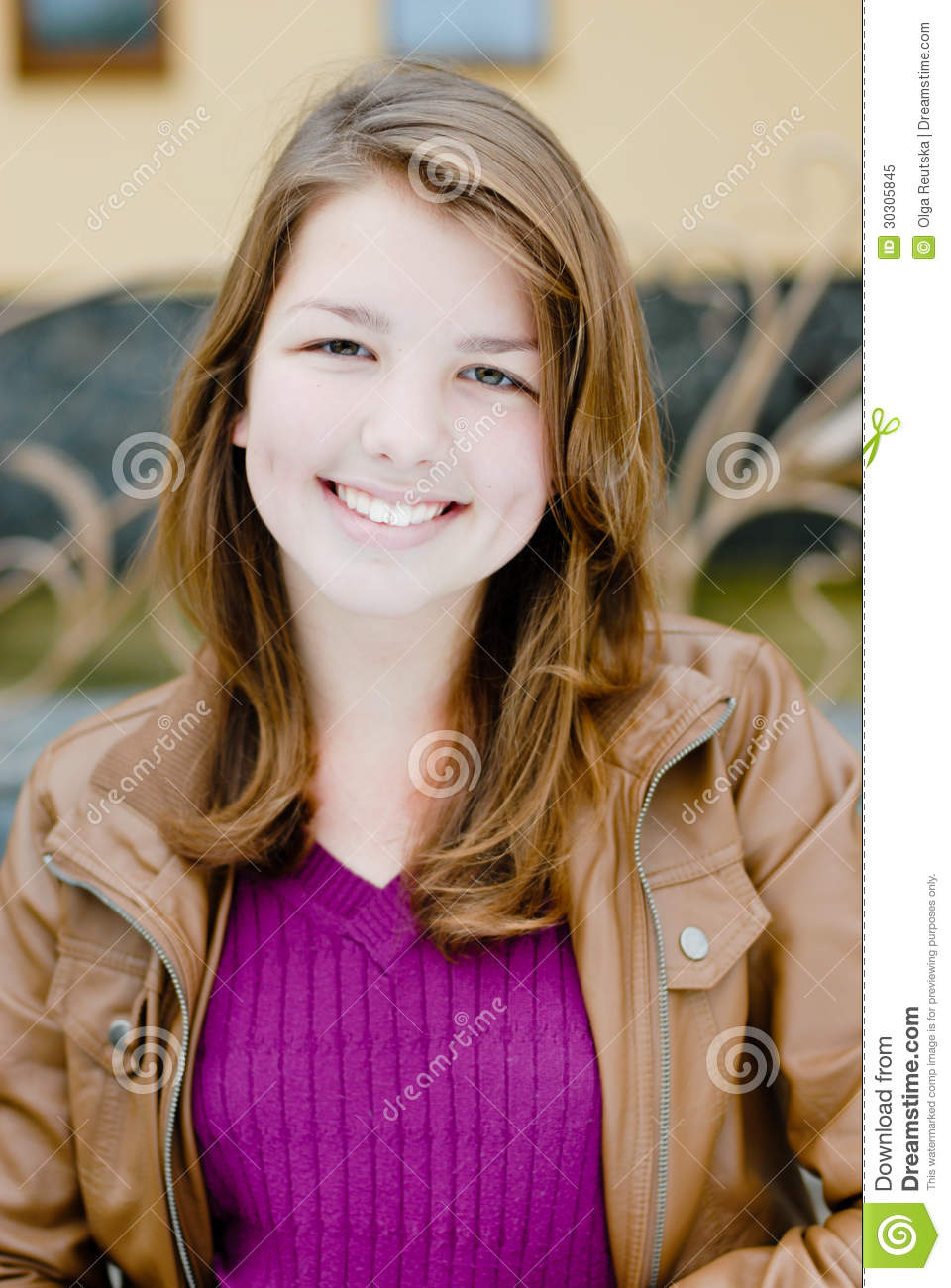 Outdoors portrait of beautiful young teen brunette girl happy smiling