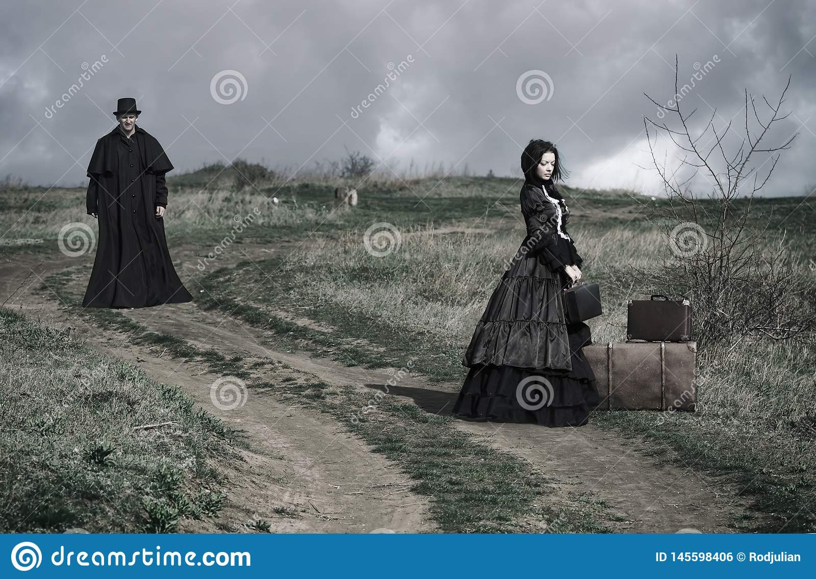 Portrait of a victorian lady in black sitting on the road with her luggage and gentleman walking down the road
