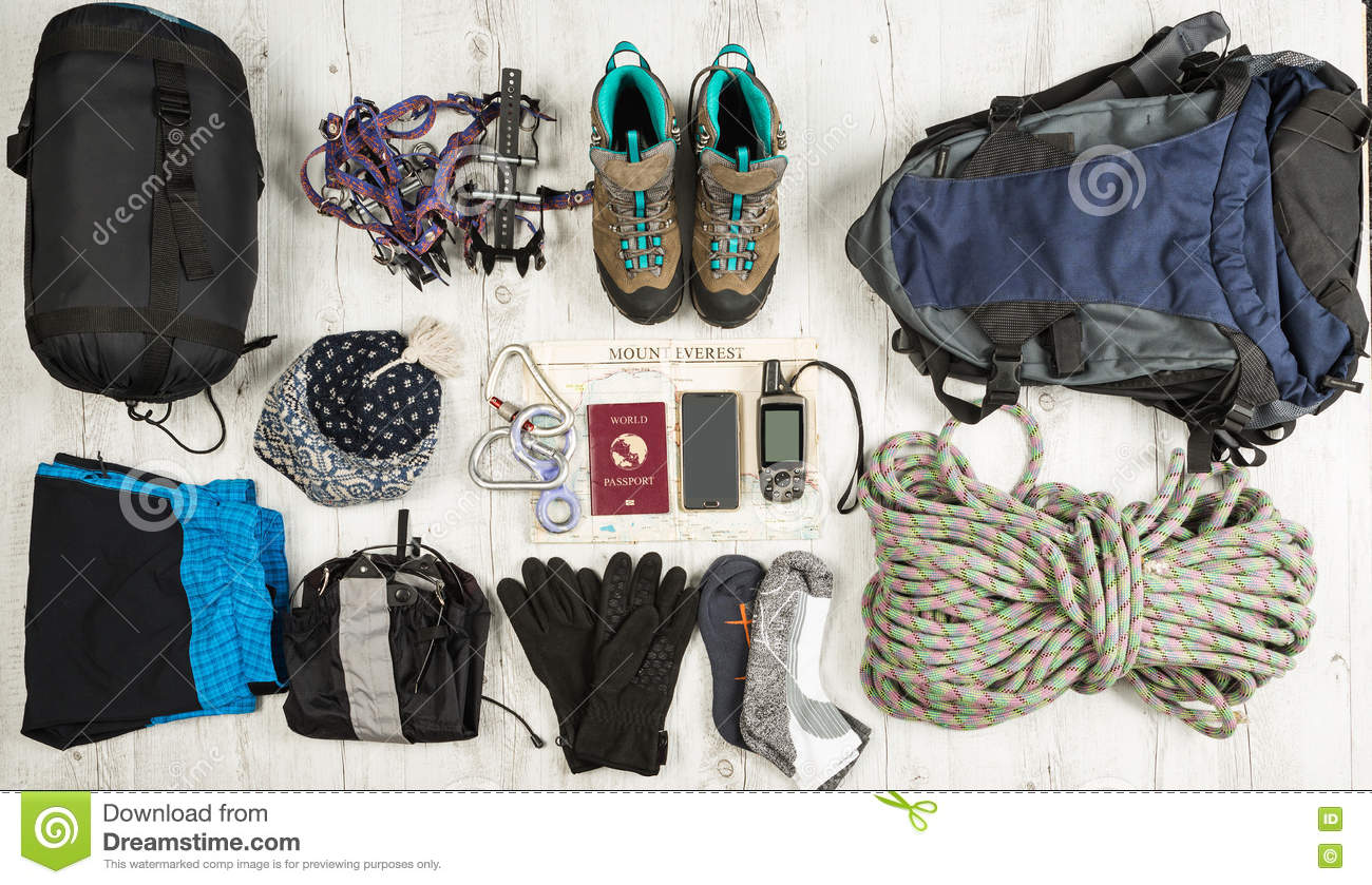 Outfit of traveler, climger, student, teenager. Overhead of essentials for modern sport young person. Different objects on wooden