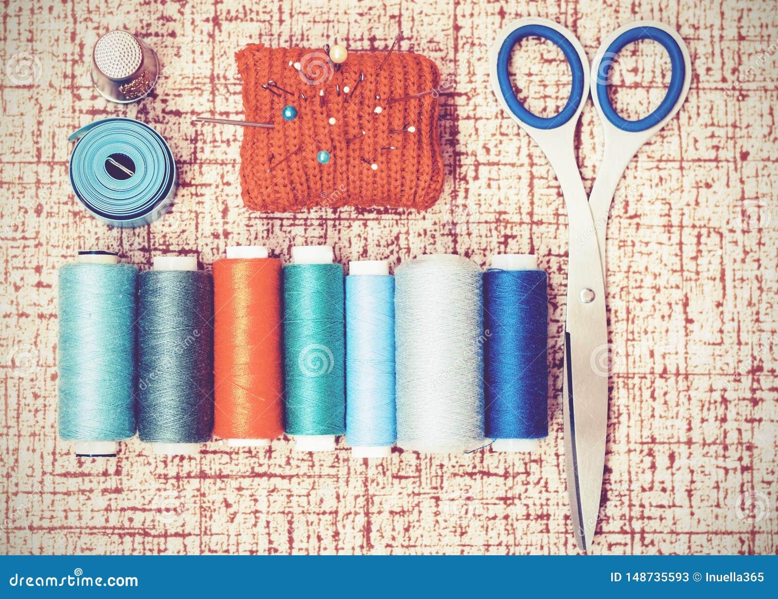 Outils pour la couture, la protection tricot?e rouge d aiguille pour coudre, les ciseaux et les bobines color?es de fil sur le fo