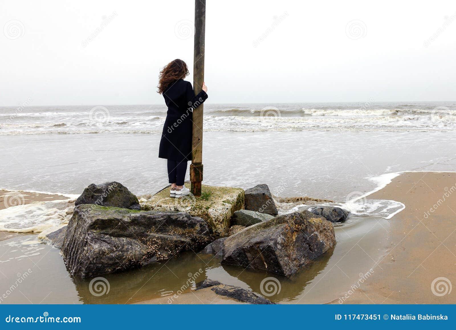 Outono encaracolado da praia da neve da costa do humor do cabelo longo do revestimento da mola do sorriso da mulher do retrato do