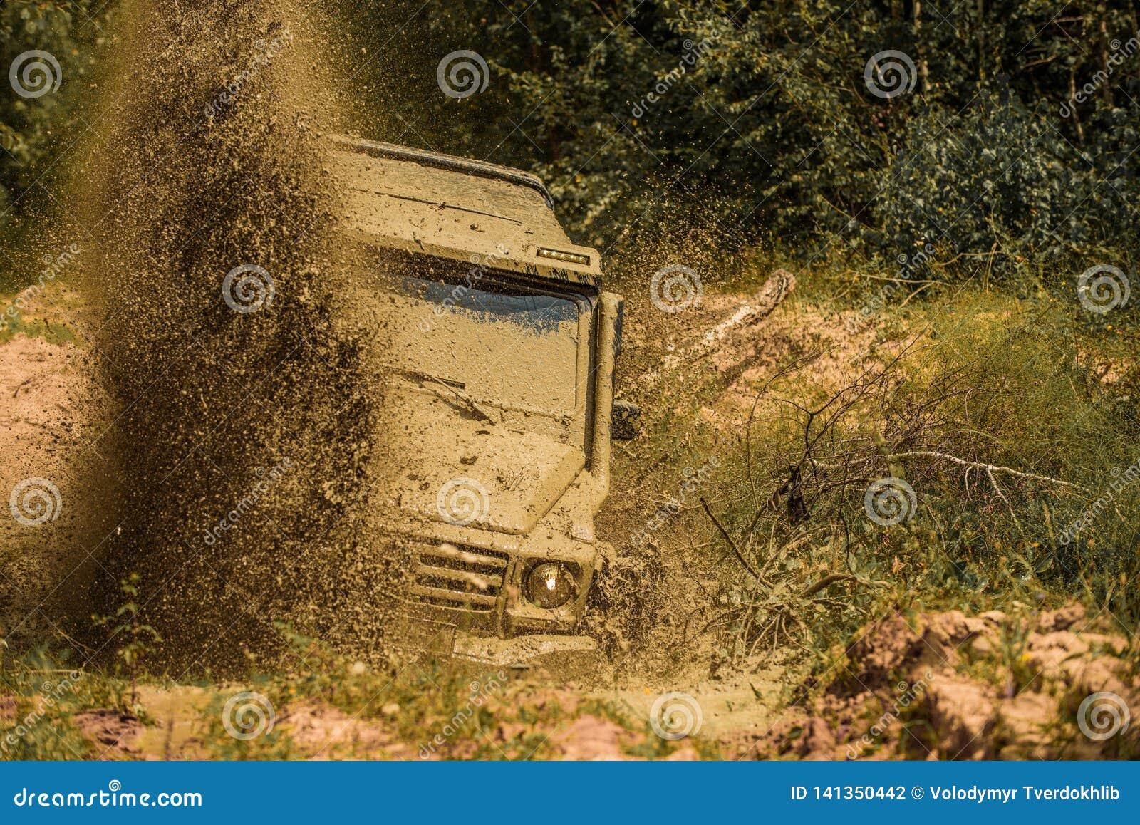 Outre du camion de sport de route entre le paysage de montagnes Mudding off-roading par un secteur de boue ou d argile humide Bou