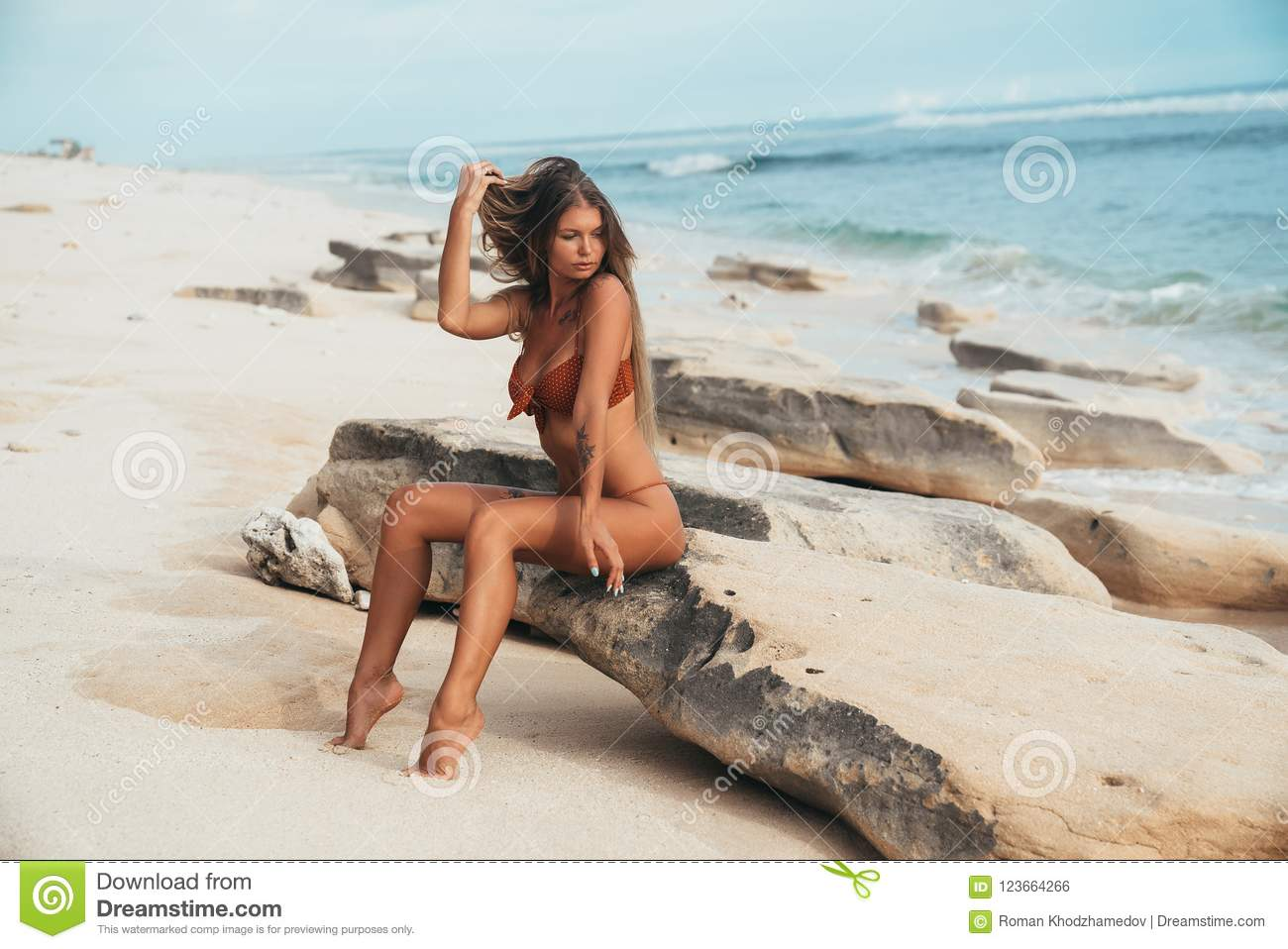 Outside, a beautiful charming attractive model girl sits on a rocky rock, enjoys the noise of the sea surf and a light