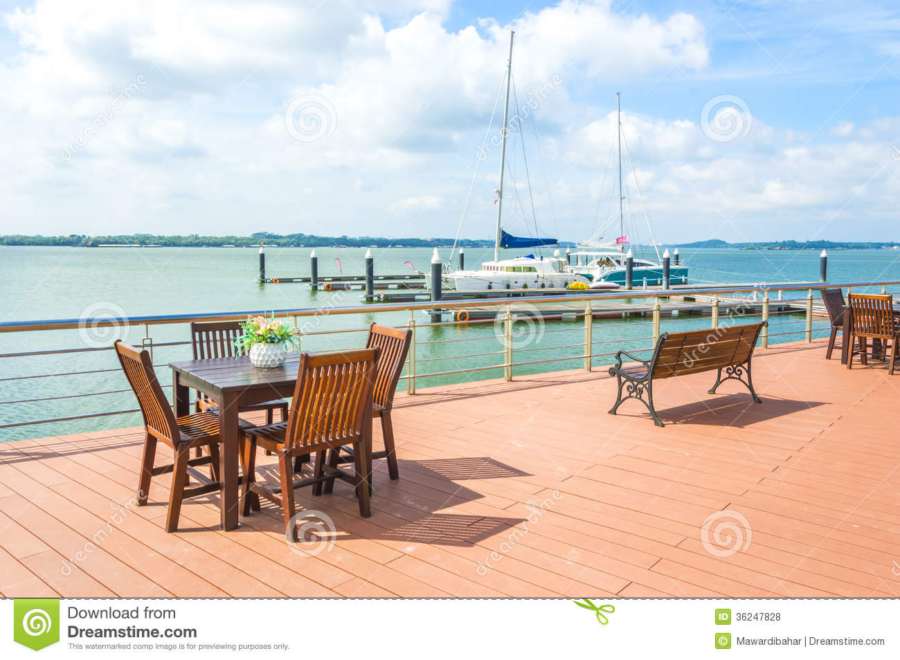 View of wooden table and chair at outdoor cafe with yatch and blue ...