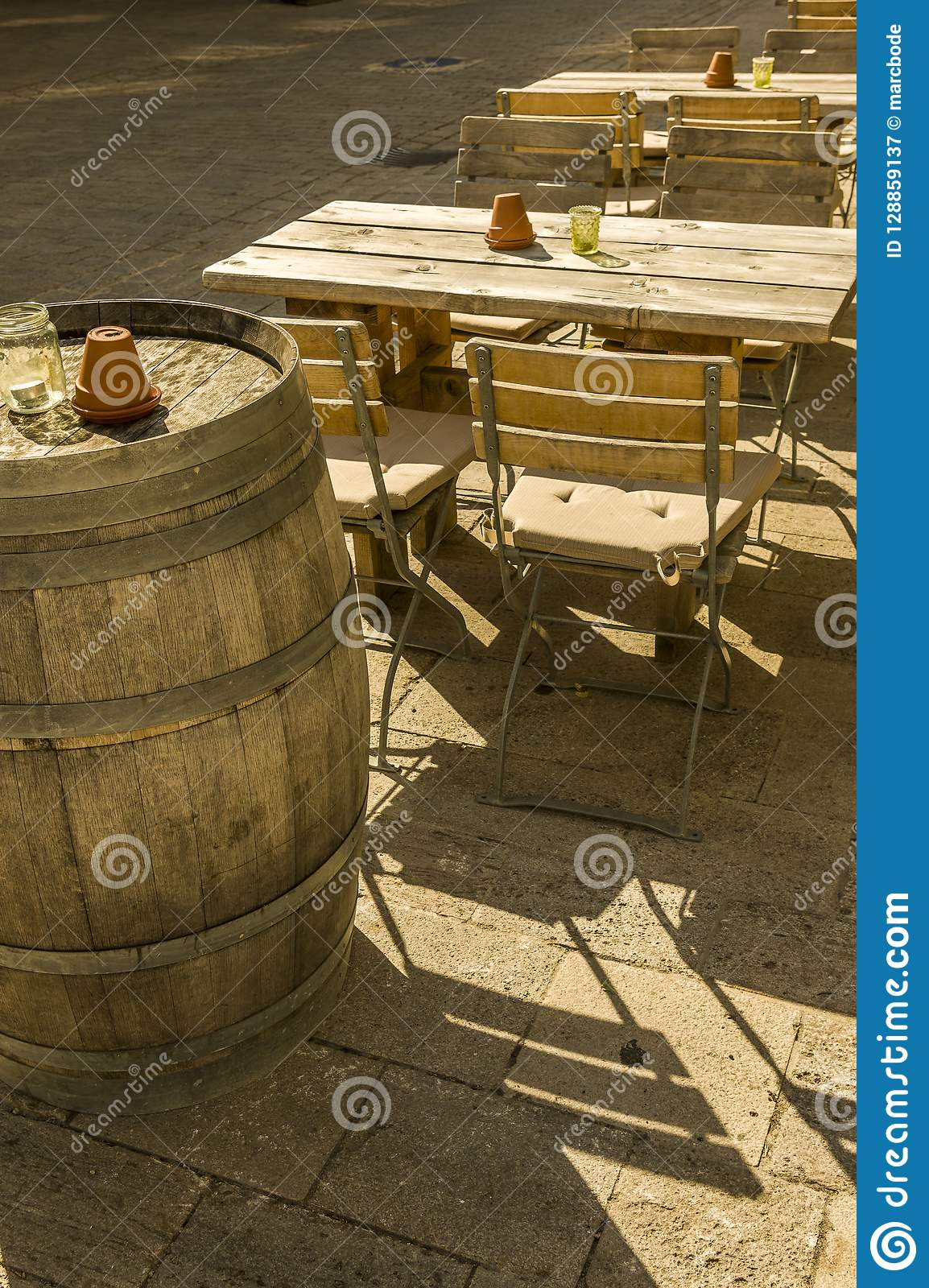 Outside seating of a wine bar with tables chairs and barrels as
