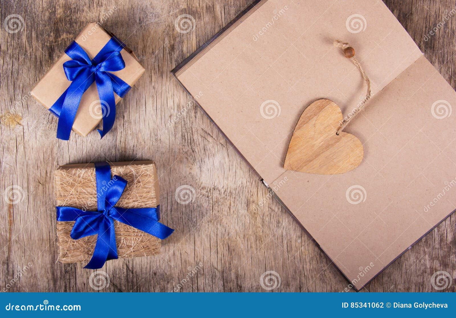 Ouvrez le carnet avec les pages vides, la valentine faite de bois et les boîtes avec des cadeaux Boîte-cadeau avec le ruban bleu