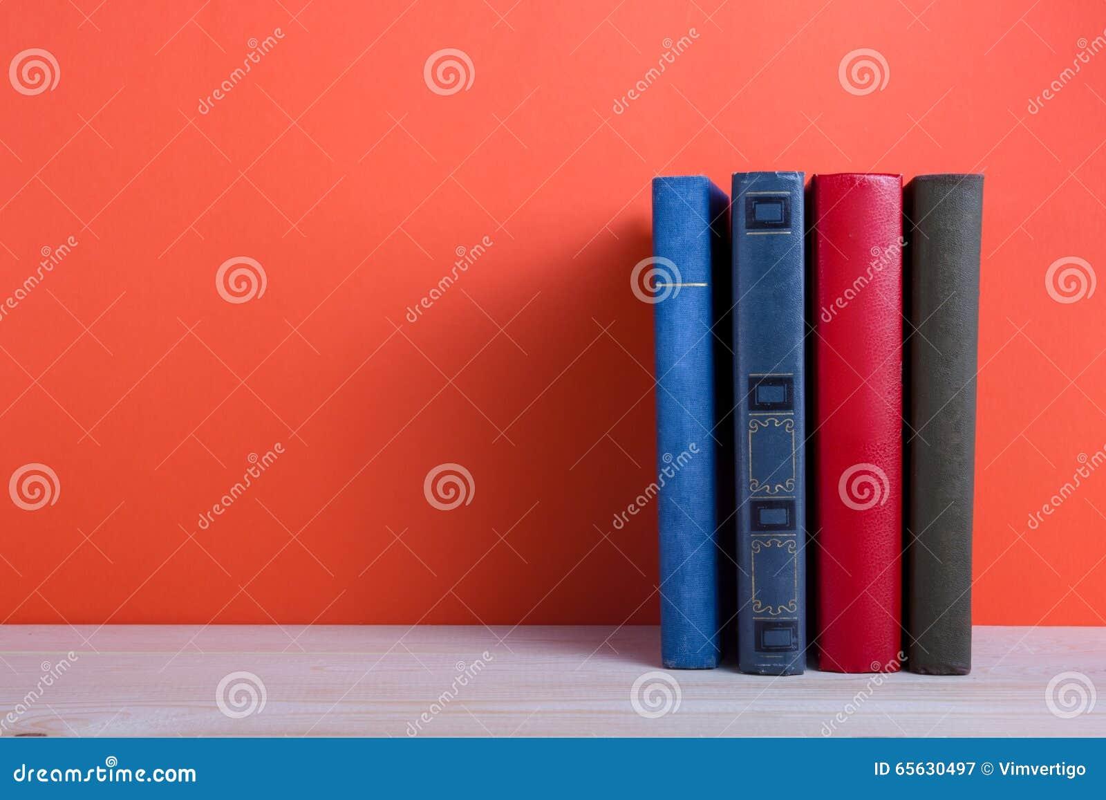 Ouvrez le livre de livre cartonné sur la table en bois de plate-forme et le fond rouge