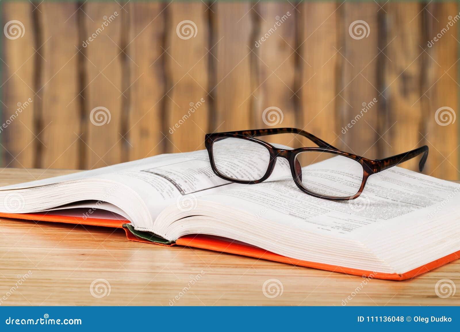 Ouvrez le livre et les verres sur la table en bois