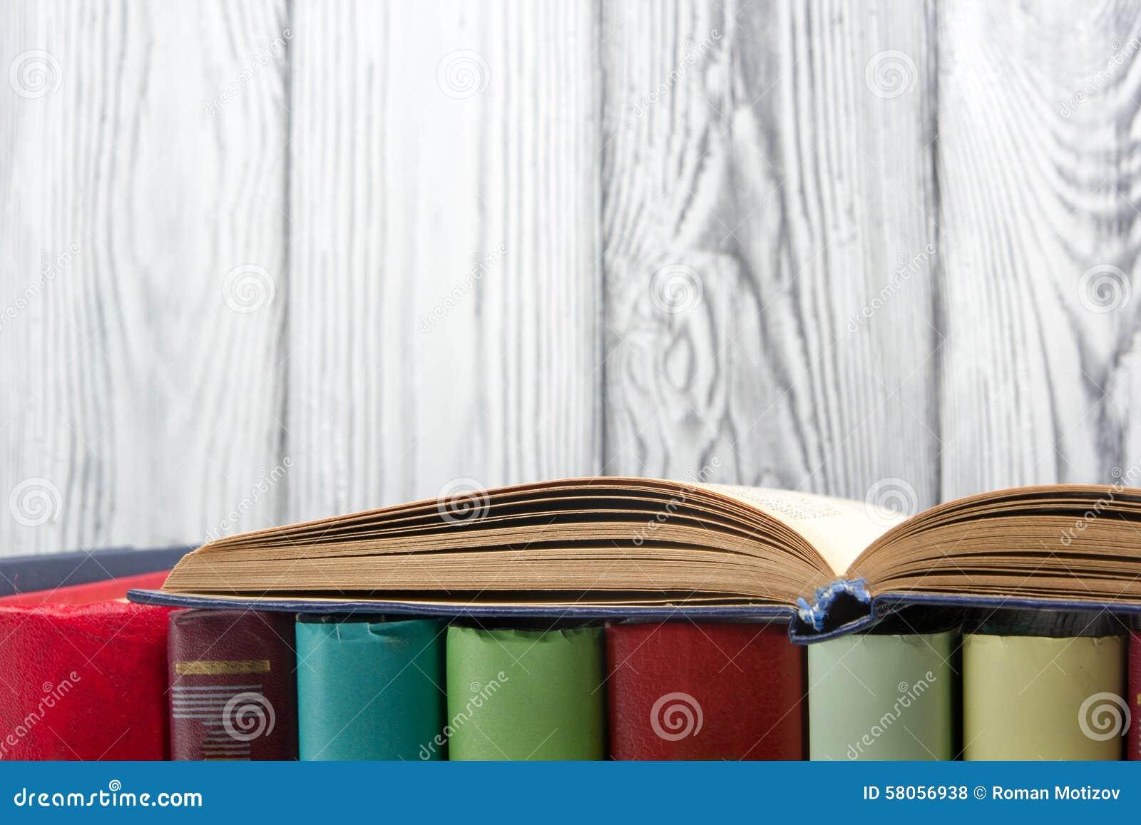 Ouvrez le livre, livres de livre cartonné sur le fond en bois De nouveau à l école Copiez l espace