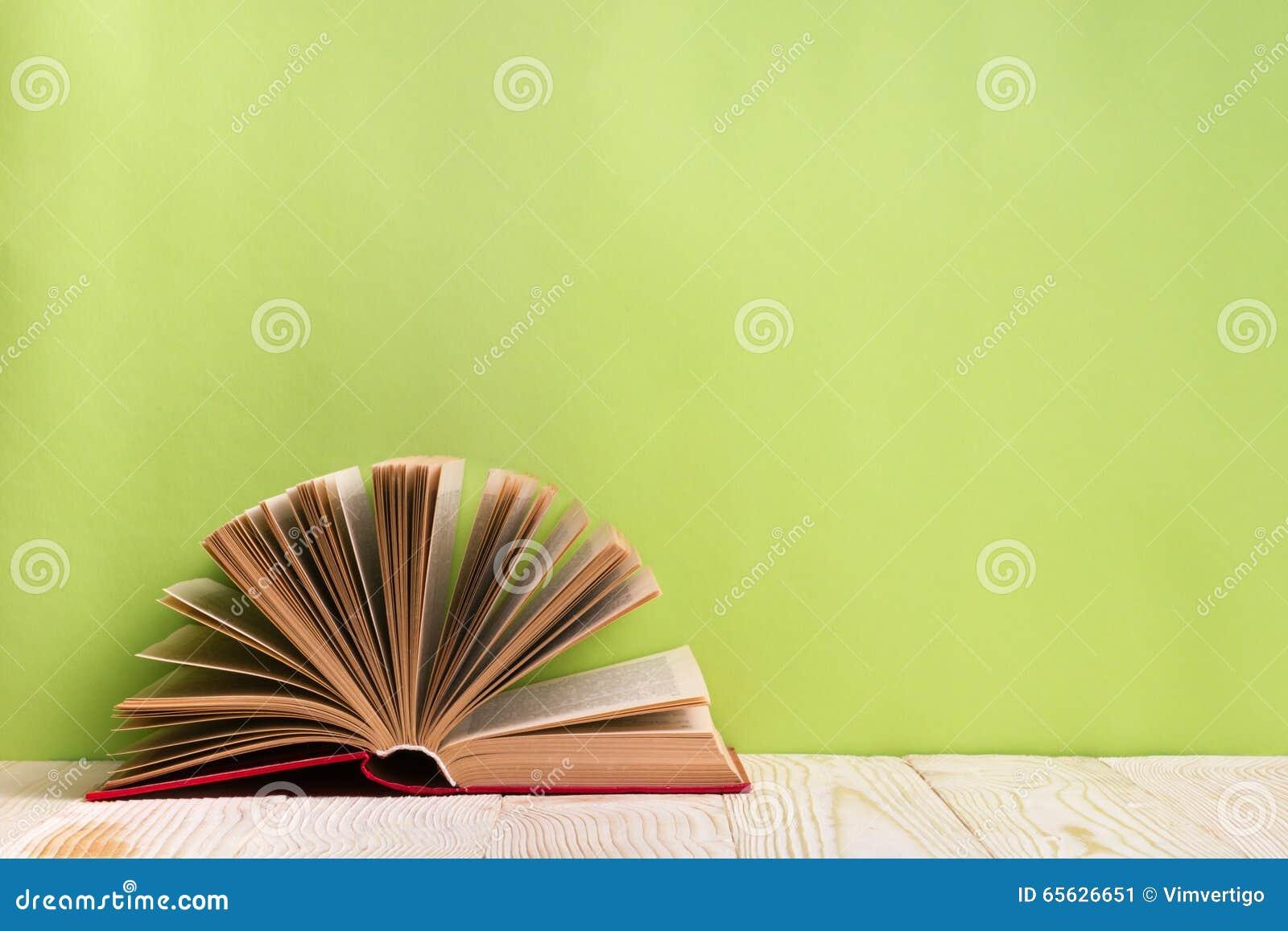 Ouvrez le livre sur le bavkground en bois vert Fond d éducation