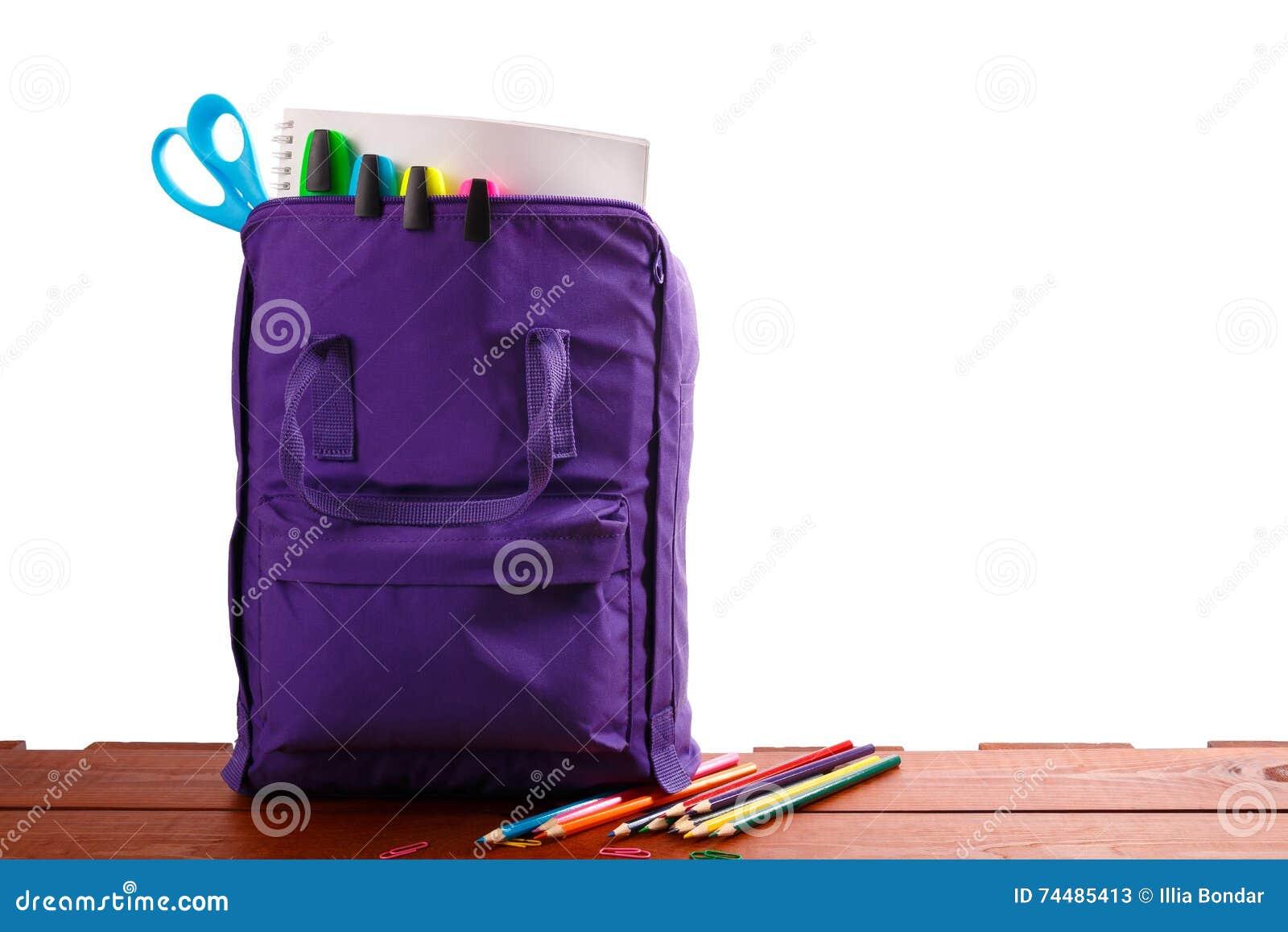 Ouvrez le sac à dos pourpre avec des fournitures scolaires sur la table en bois De nouveau à Fin vers le haut