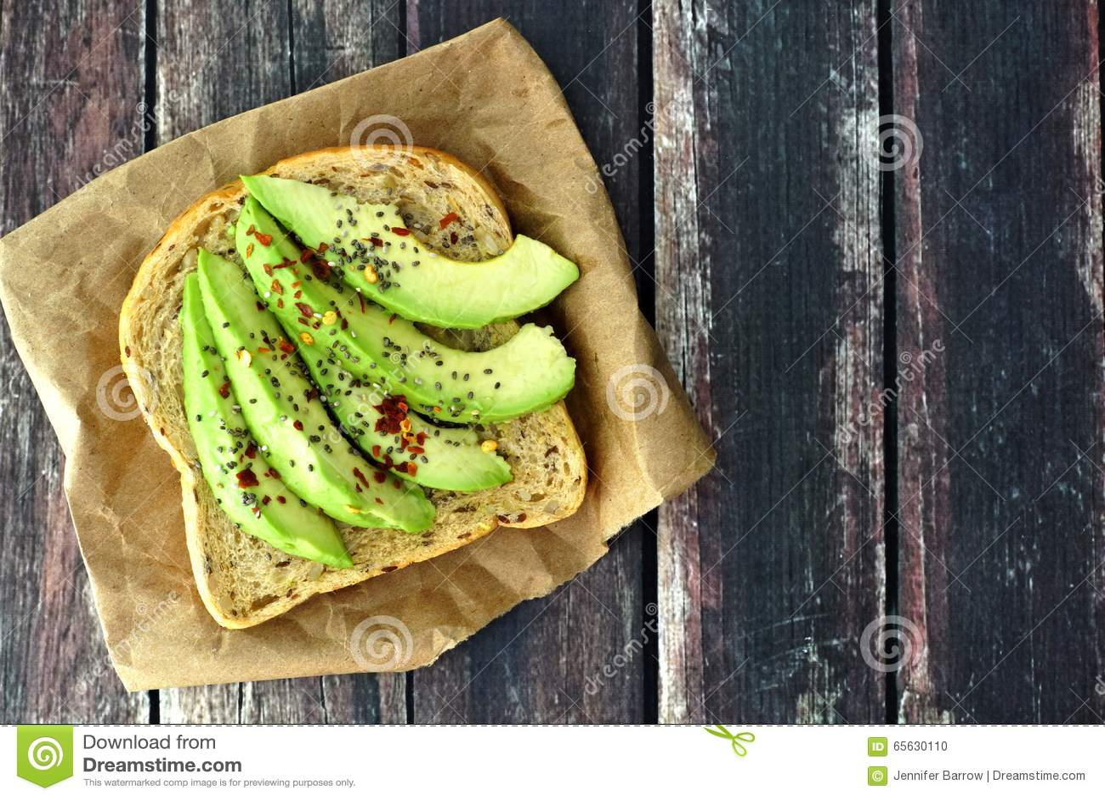 Ouvrez le sandwich à avocat sur le papier contre le bois rustique