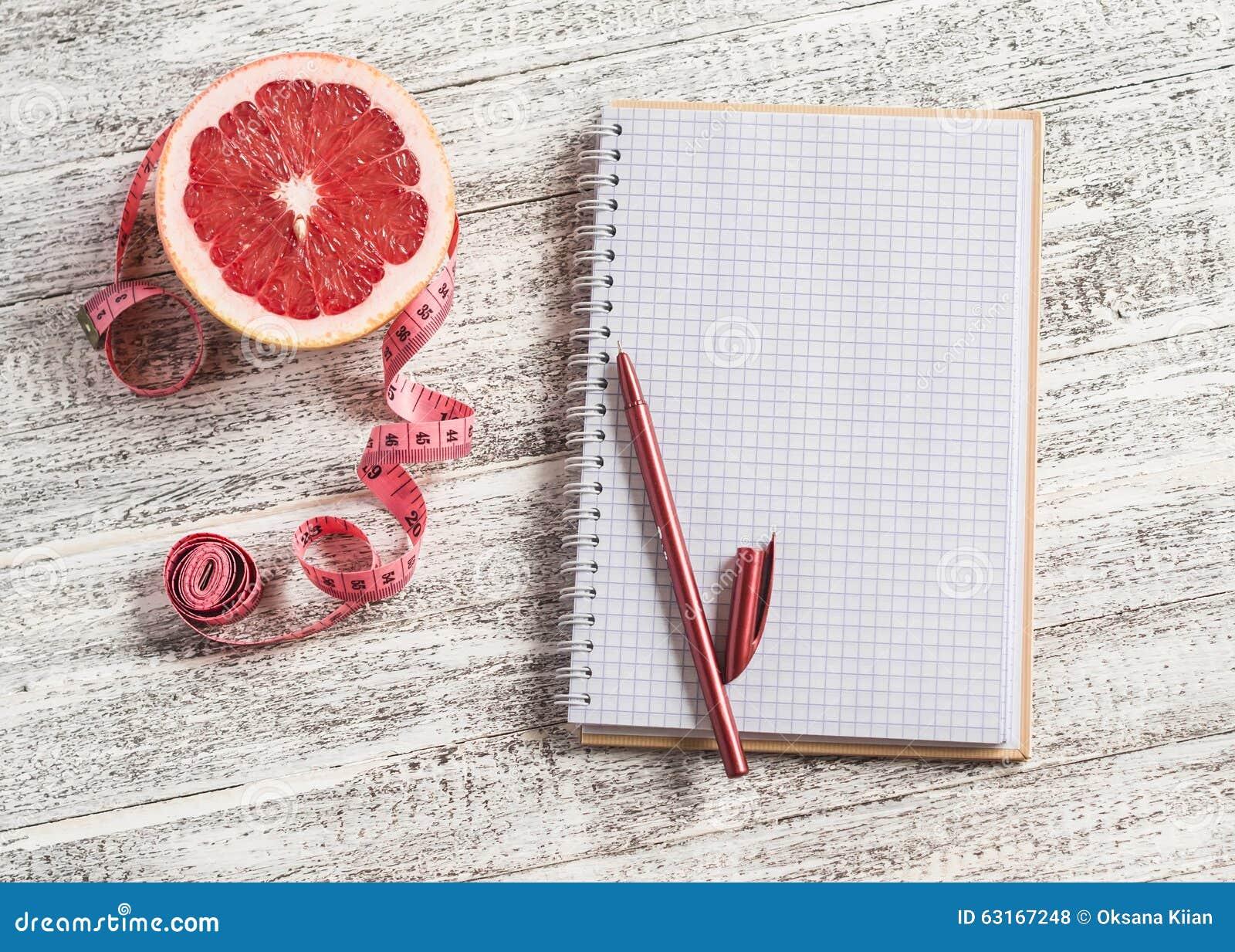 Ouvrez un bloc-notes vide, un pamplemousse et une bande de mesure sur une table en bois légère Le concept de la nutrition saine,