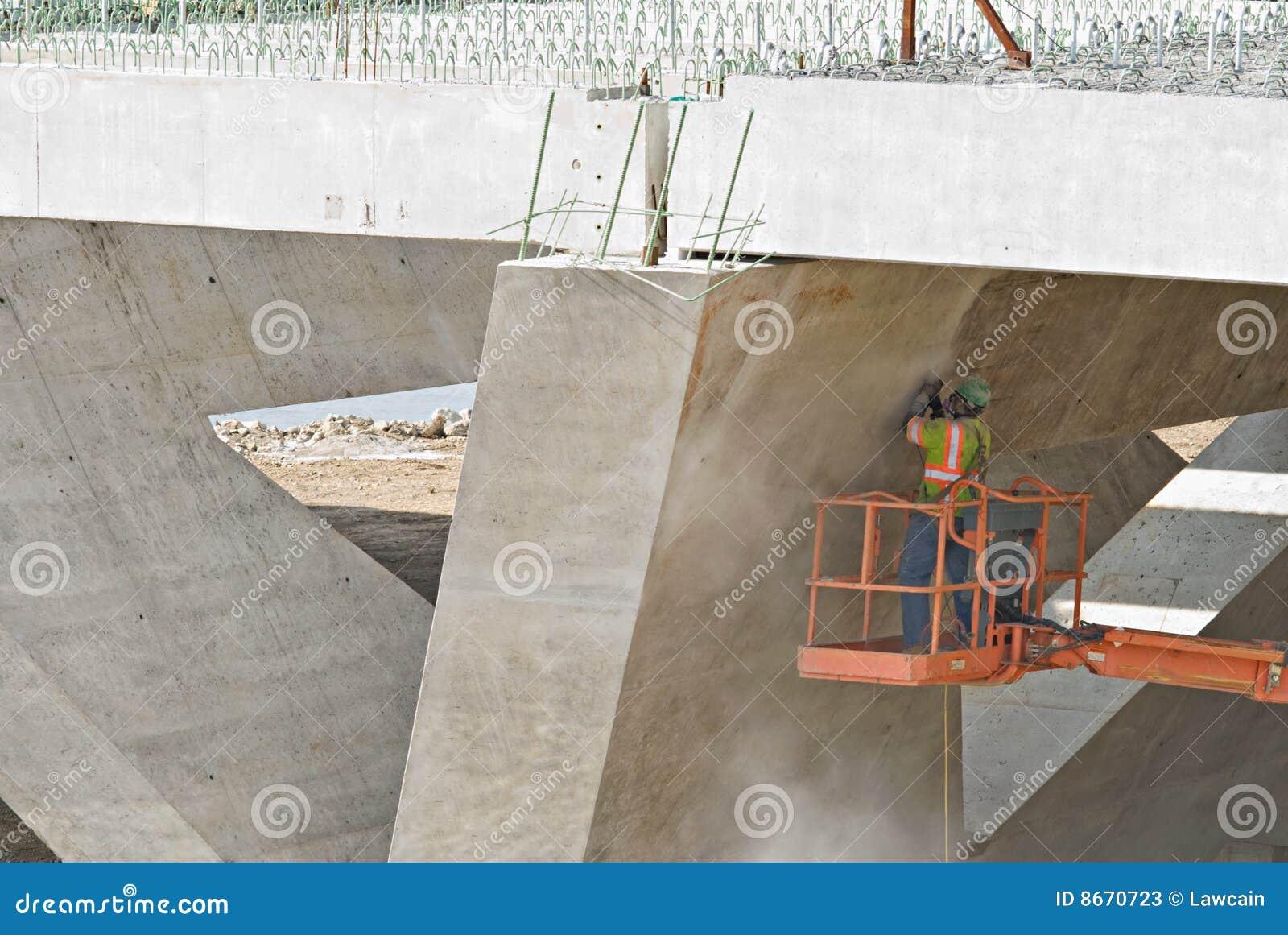 Ouvrier sablant sous la passerelle
