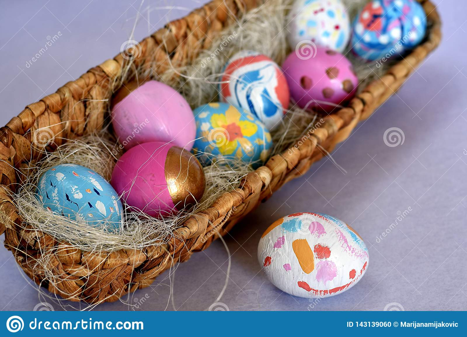 Oval basket full of brightly colored Easter eggs with one white spotted egg beside