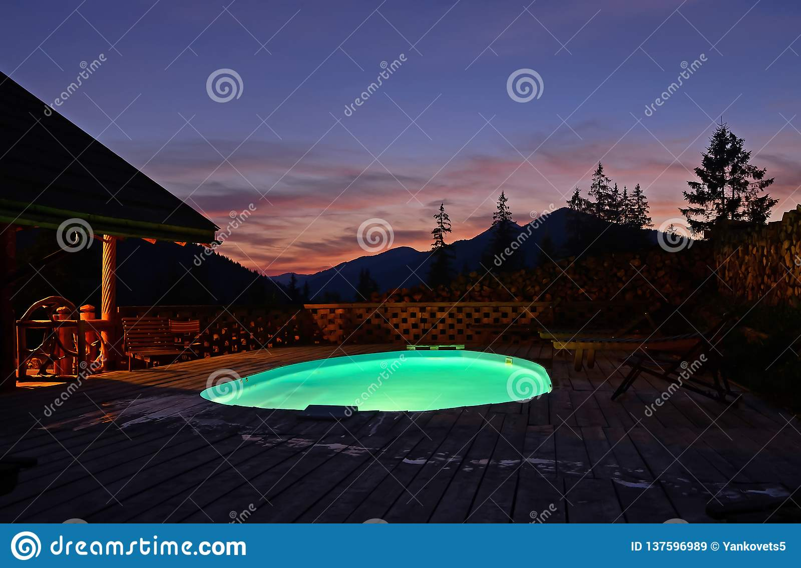 Oval open-air swimming pool high in the mountains against the backdrop of the beautiful summer sunset and mountains. The