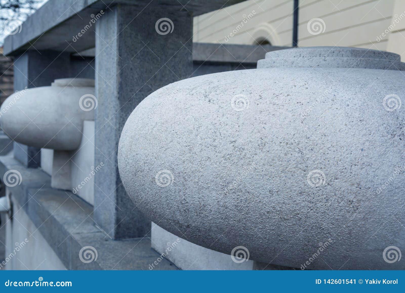 Ovals da pedra decorativa do granito cinzento Detalhe do cenário da cerca Fundo bonito com matiz azul