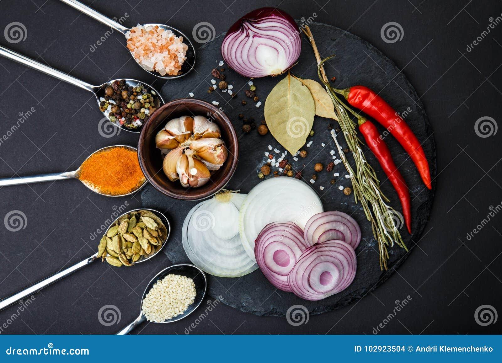 Ovanför sikt På ett runt bräde, skarpa grönsaker och en sked av kryddor