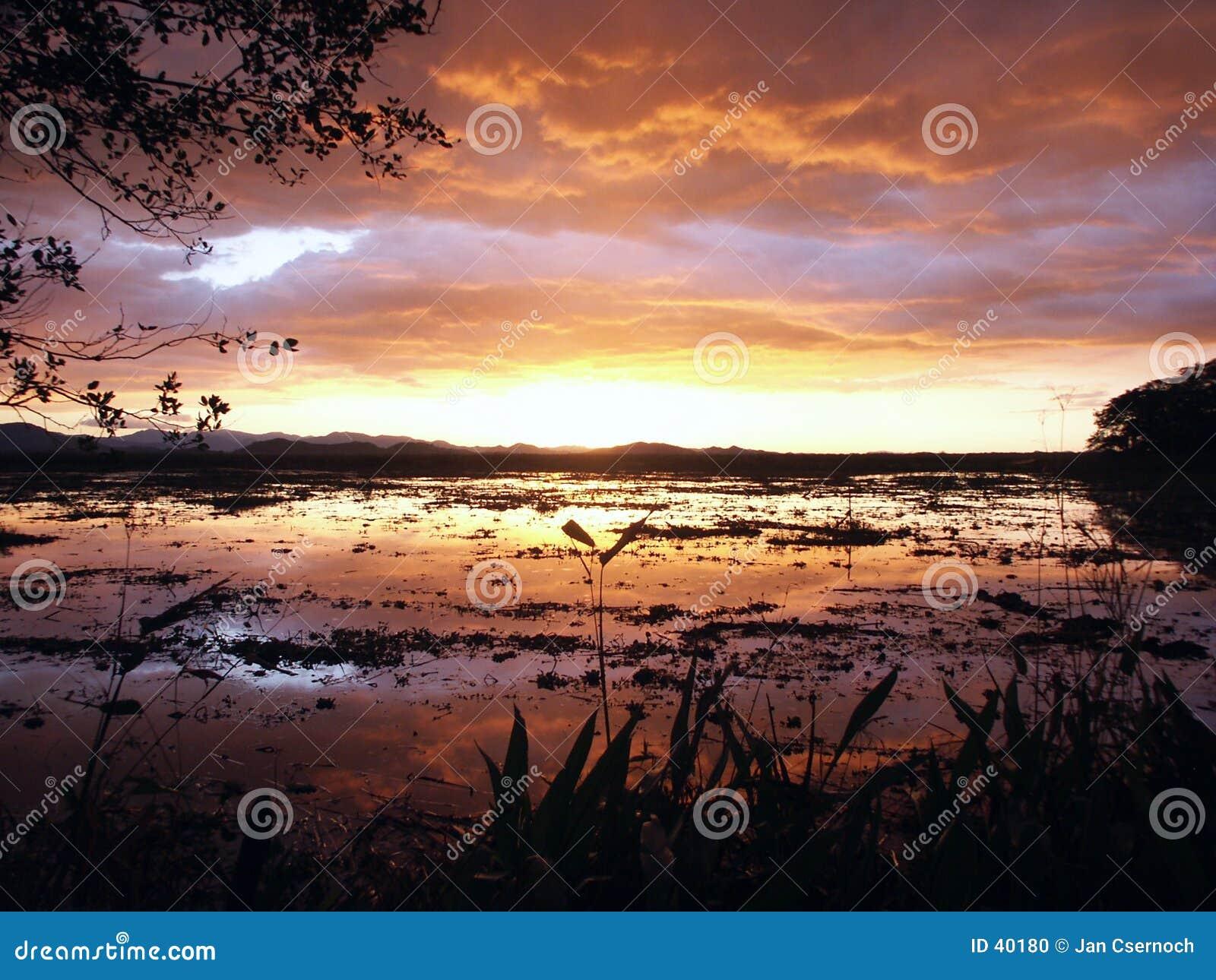 Ovanför stormig solnedgång för lake