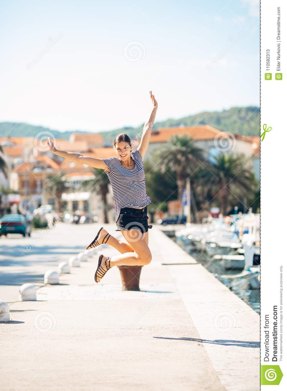 Over exited happy woman jumping in the air out of happiness. Vacation time concept. Seaside coastal vacation excitement. Woman in
