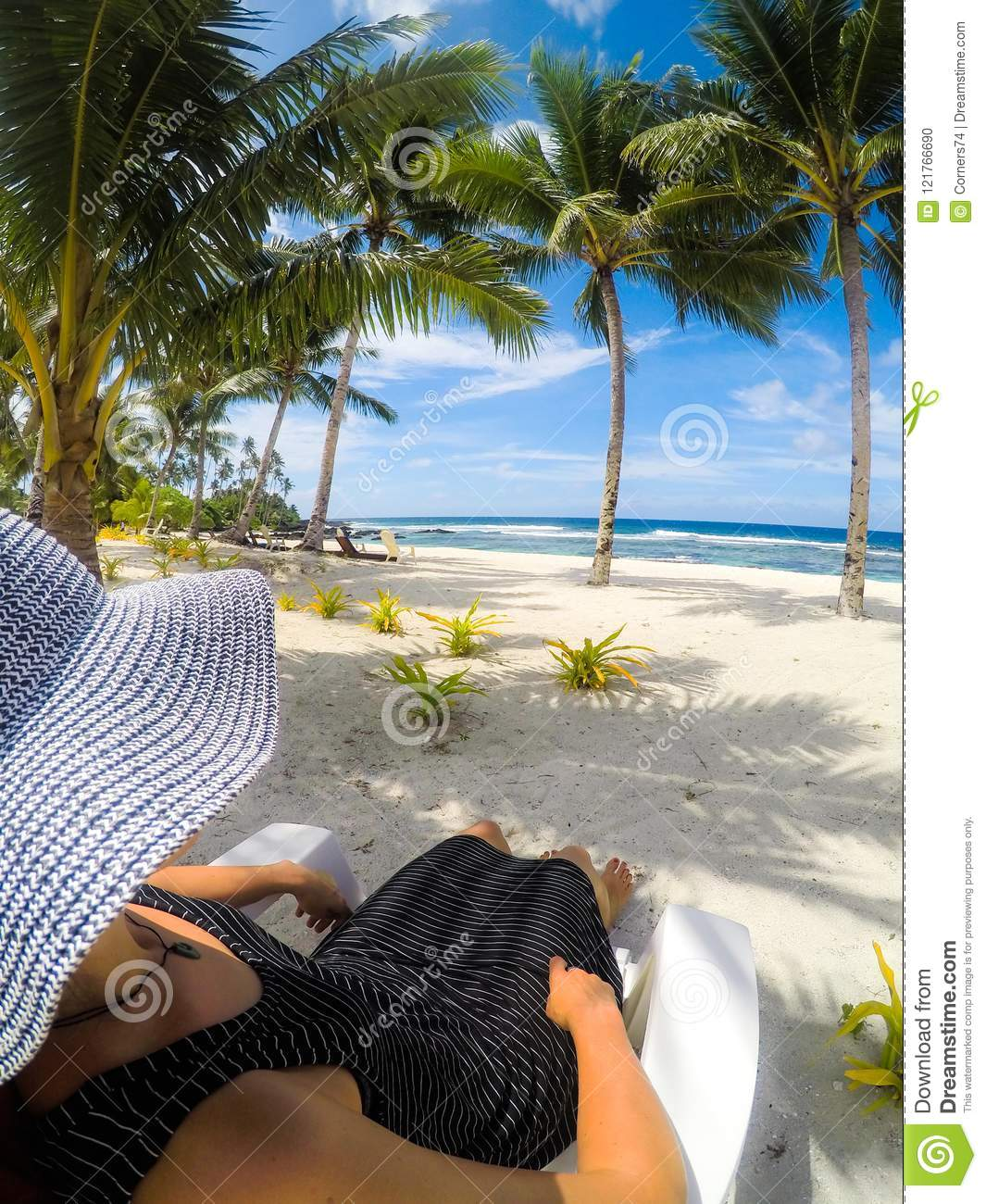 Over Shoulder POV: Woman In Hat And Dress On Sun Lounger