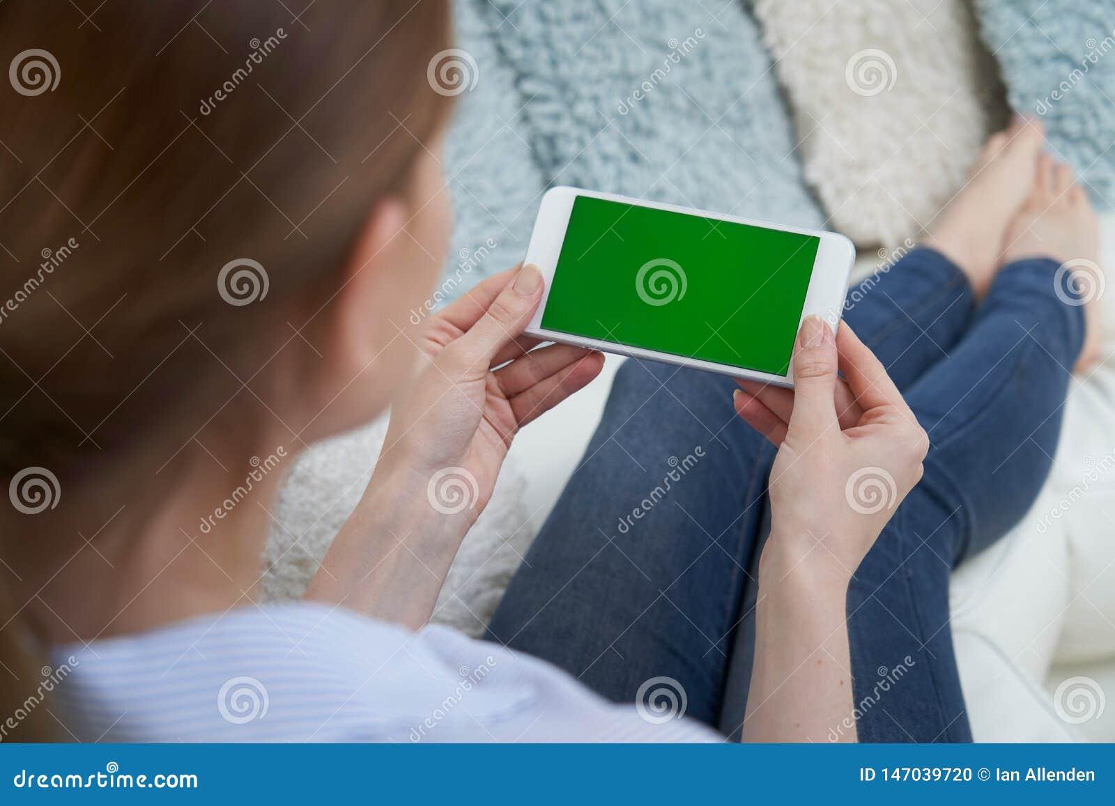 Over The Shoulder Weergeven van Vrouw het Liggen op Sofa Using Green Screen Mobile-Telefoon thuis